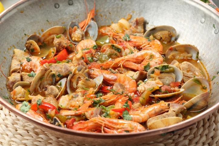 Traditionele koperen cataplana gevuld met venusschelpen, gamba's en stukjes vis