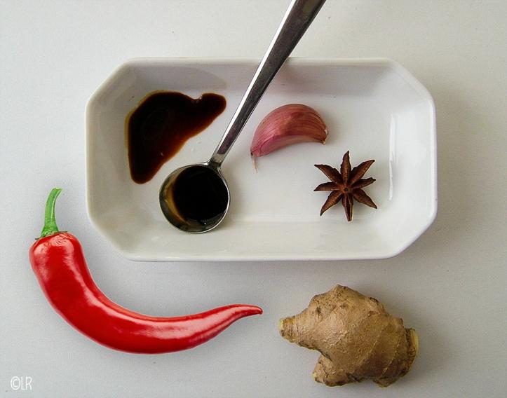 Lepeltje ketjap manis met een teen roze knoflook, een steranijs, stukje gemberwortel en pepertje