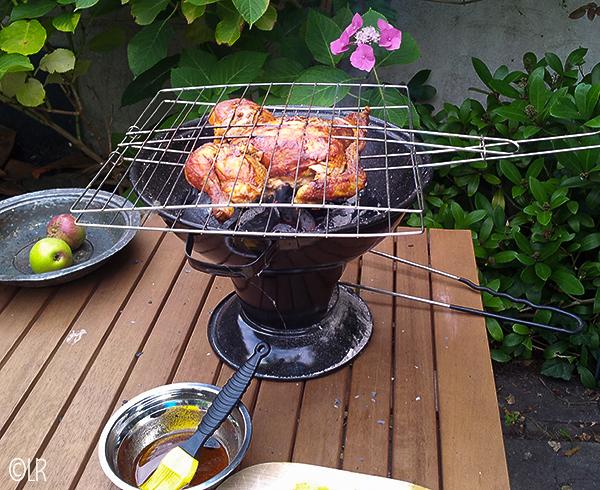 Bruin gegrilde kip op een kleine barbecue met een schaaltje piri-piri saus