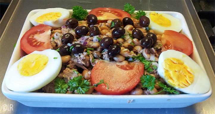 Kleurige schotel met bonen vermengd met tonijn en opgemaakt met tomaat, hardgekookte eieren en olijven