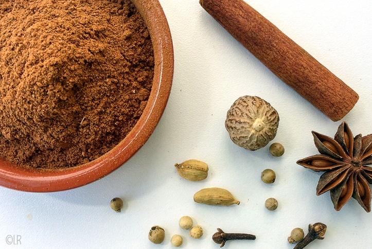 Schaaltje specerijen met ernaast een pijpje kaneel, nootmuskaat, steranijs, kardemom, peper en kruidnagel.