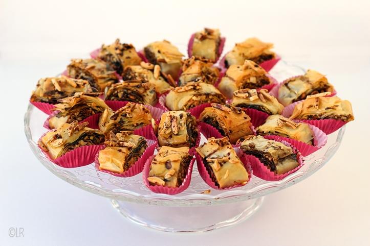 Schaal met rolletjes baklava in rode papieren cakevormpjes.