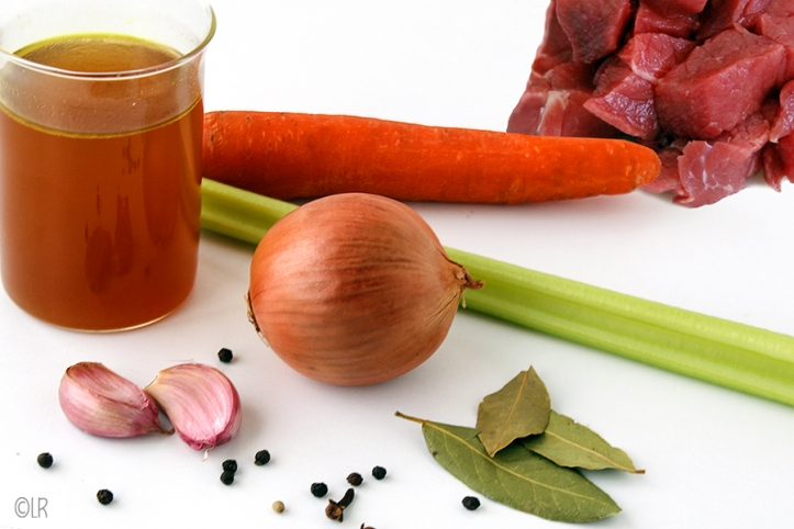 Glas runderfond met ernaast wat van de ingrediënten om het te maken: rundvlees, wortel, bleekselderij, ui, knoflook, peper, laurier en kruidnagel.