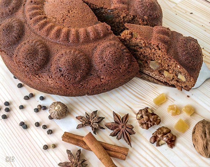 Kruidkoek uit de Zeeuwse knop met gember en walnoten. Er omheen liggen specerijen die voor de koekkruiden zijn gebruikt.