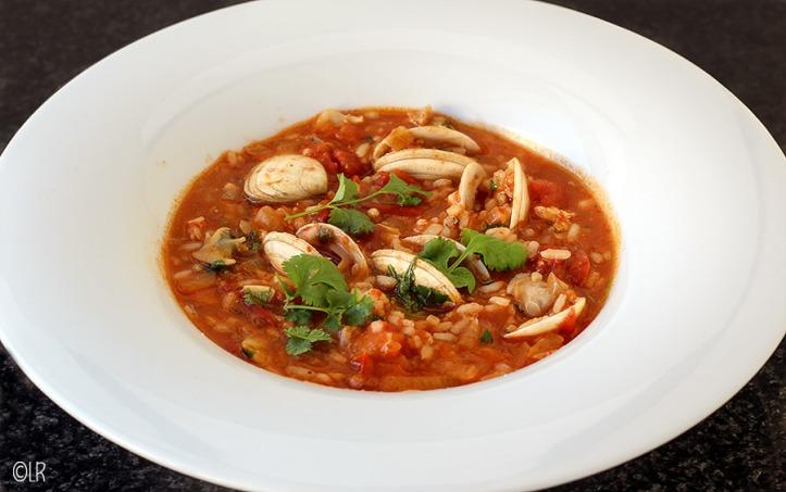 Diep bord met tomaten-risotto en venusschelpen gegarneerd met korianderblad.