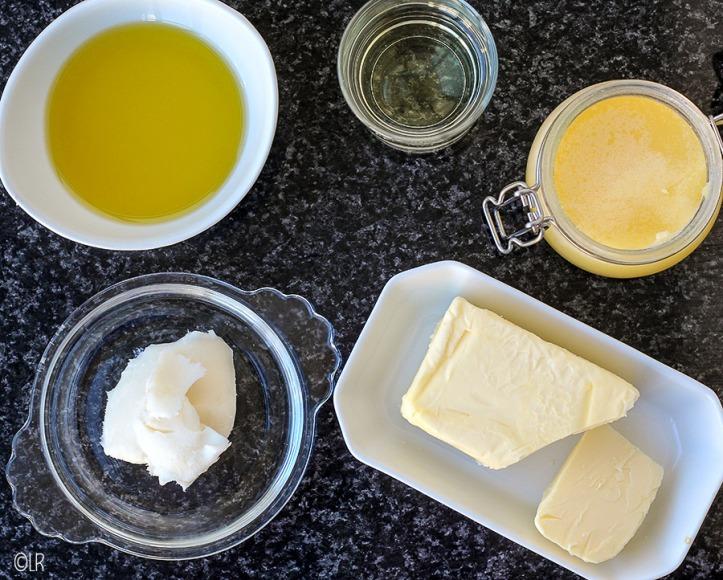 Met de klok mee: Schaaltje olijfolie, glas zonnebloemolie, potje geklaarde boter, schaaltje roomboter en een schaaltje reuzel.