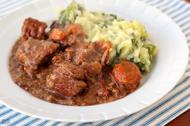 Smakelijke stoofschotel van rundvlees met ernaast een stamppot aardappel-kool