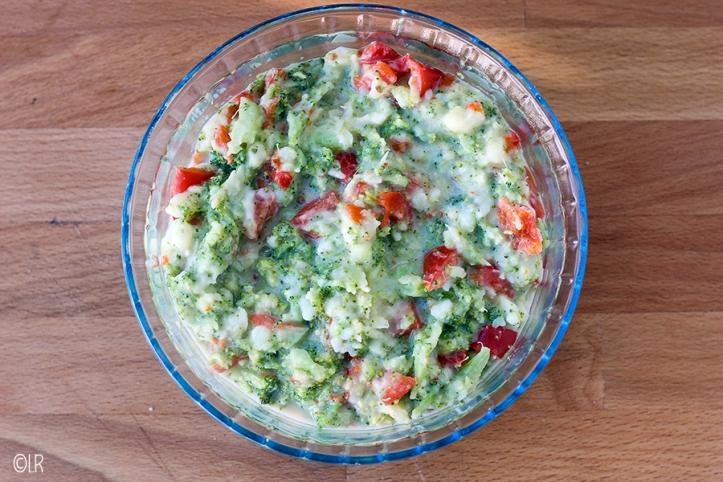 Schaal met kleurige grove broccolistamppot met stukjes paprika.