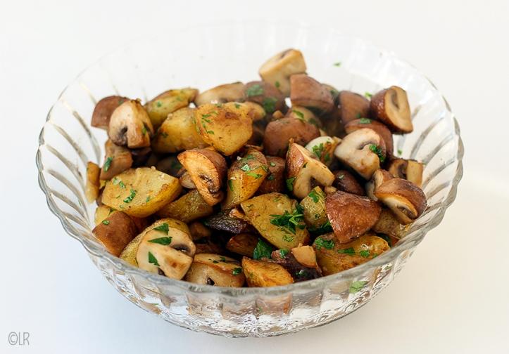 Glazen schaal met knapperig bruin gebakken aardappeltjes, kastanjechampignons, knoflook en peterselie.