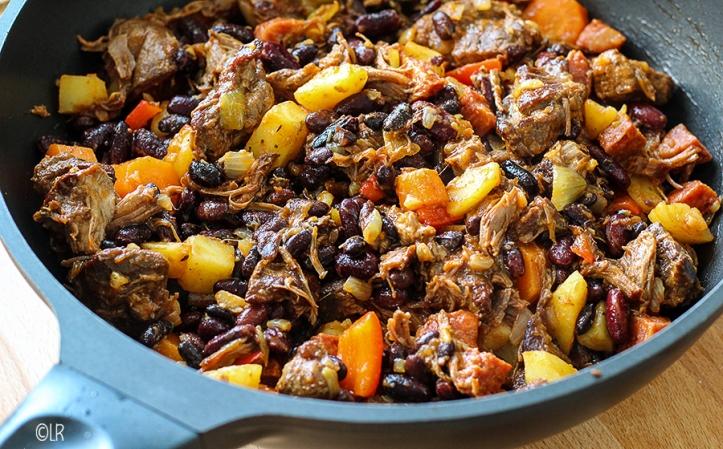 In de wok een heerlijk eenpansgerecht van donkere bonen met gaar soepvlees en groenten.
