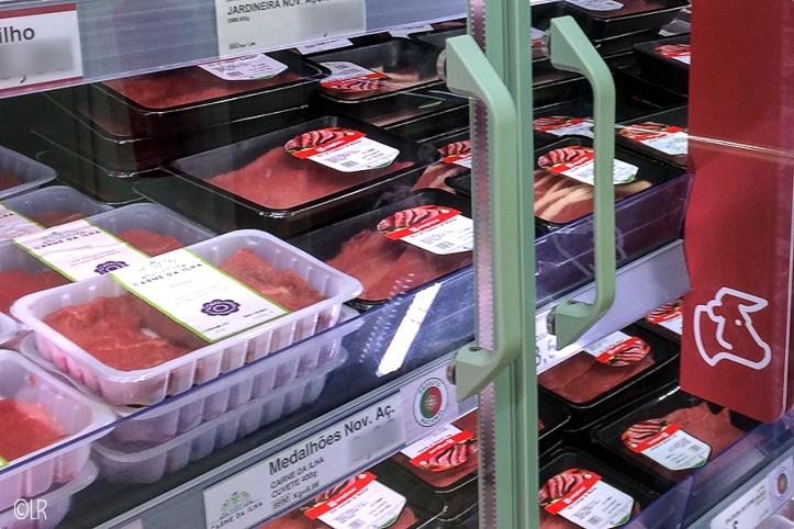 Het koelvak van de supermarkt vol met pakjes rundvlees.