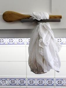Een kaasdoek gevuld met kwark die met een houten lepel is opgehangen aan het handvat van een keukenkastje