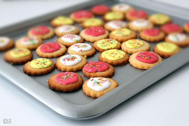 Een bakblik vol vrolijk gekleurde koekjes, leuk om uit te delen of voor een feestje!