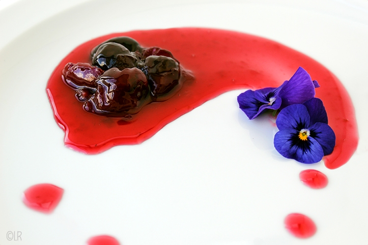 Ingemaakte kersen op een mooie zware suikersiroop gedecoreerd met een paar viooltjes.