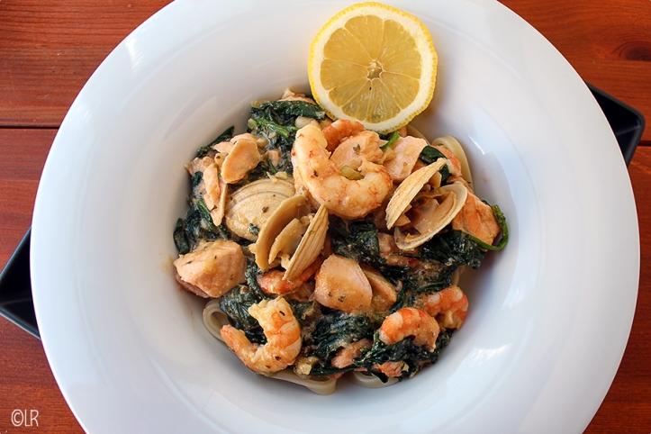 Verrukkelijke saus met gerookte zalm velouté, garnalen, schelpjes en spinazie op een bedje van lintspaghetti.
